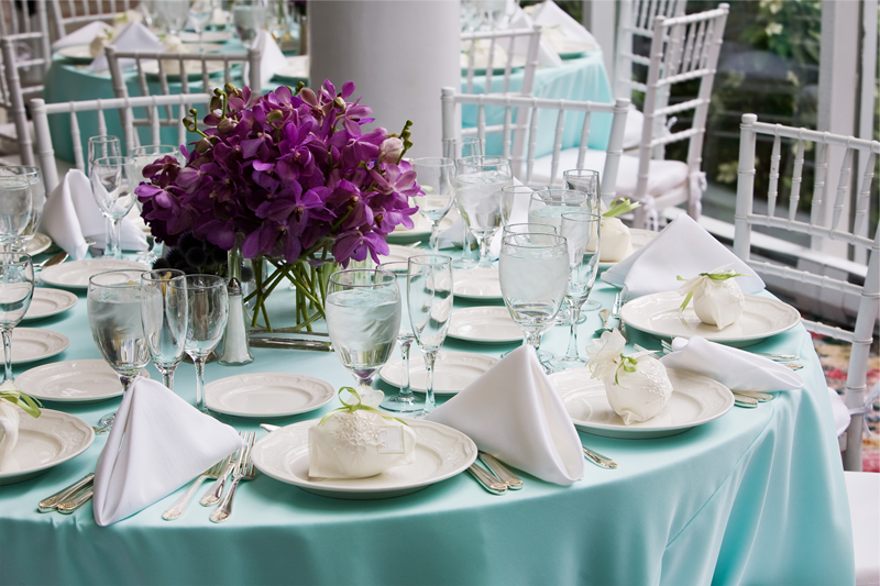 Table setting with blue table cloth and white plates and napkins