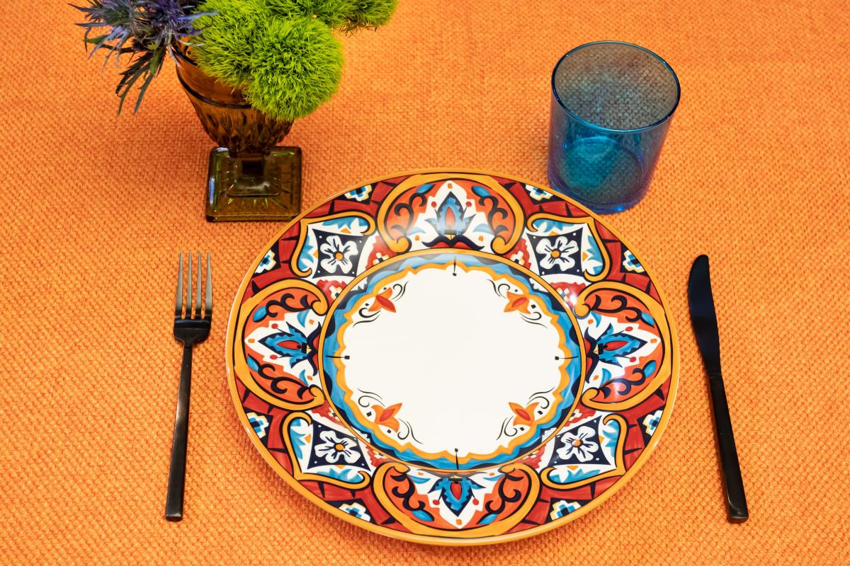Valencia Base Plate with Light Blue Double Rocks and Black Matte Flatware on Orange Basketweave